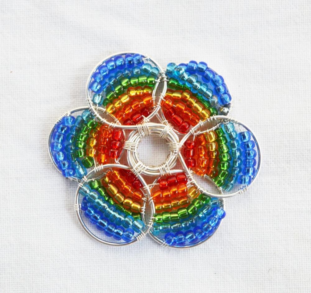 4c763599a8 Legyél Te a nyári fesztiválok sztárja ezzel a szemkápráztató, szivárvány  színekben pompázó virág medállal. Most megmutatjuk, hogyan készítheted el!