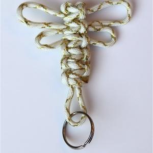 Szitakötő alakú paracord kulcstartó - fehér-arany, Táska, Divat & Szépség, Kulcstartó, táskadísz, Fonás (csuhé, gyékény, stb.), Csomózás, Méret:\nHossz: kb. 10cm karikával.\nSzélesség: szárnyaknál kb 8cm.\nKarika: 25mm átmérőjű\n\nLeírás: Szit..., Meska