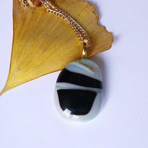 Ásványos üveg medál, Ékszer, Nyaklánc, Medálos nyaklánc, Üvegművészet, Ékszerkészítés, Világoskék, fekete és fehér színű üvegből készült medál arany színű láncon. A medál 2,2 cm széles, a..., Meska