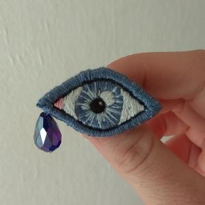 Kék szem I. - Hímzett bross, Ékszer, Kitűző, bross, Ékszerkészítés, Hímzés, Lenvászonra, kézzel hímeztem a mintát. Háta kék színű filc, amire kitűzőalapot erősítettem.\nA könnyc..., Meska