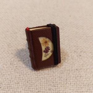 Bőrös könyvgyűrű (5), Ékszer, Gyűrű, Könyvkötés, Ékszerkészítés, Mérete: 2.8 x 2 cm, 72 oldalas. Sárga és beige  színű papírból, kézzel fűzött, igazi minikönyv, mely..., Meska