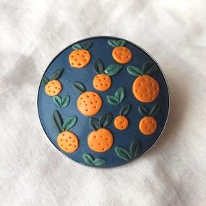 Gyurma kitűző - narancsos (M), Ékszer, Kitűző és Bross, Kitűző, Gyurma, Süthető gyurmából készült, lakkozott kitűző nemesacél alapon.\nÁtmérője: 3 cm., Meska