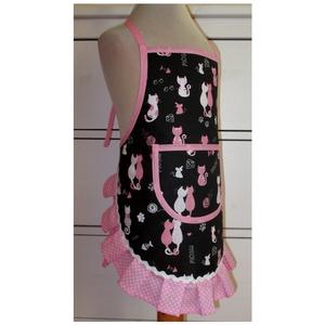 Lánykötény (rózsaszín cica /3-5 év), Otthon & lakás, Konyhafelszerelés, Kötény, Varrás, Ennek a köténynek az alapja egy fekete színű pamutvászon, melyen rózsaszínű és fehér cicák, valamint..., Meska