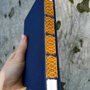 Kék jegyzetfüzet narancssárga szövött gerinccel, Művészet, Könyvkötés, Szövés, Egyedi, A6-os méretű jegyzetfüzet, fehér lapokkal, kék borítólappal, nyitott, szőtt narancssárga min..., Meska