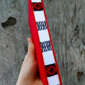 Piros könyv fekete piros díszítéssel, Művészet, Más művészeti ág, Könyvkötés, Szövés, A6-os méretű, piros borítójú, fehér lapos, nyitott, fekete varrással és piros szövéssel díszített ge..., Meska