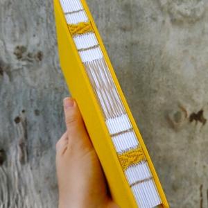 Sárga könyv, Művészet, Más művészeti ág, Könyvkötés, Szövés, A6-os méretű, sárga borítójú, fehér lapos, nyitott, bézs varrással és sárga hímzéssel díszített kisk..., Meska