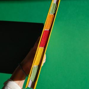 Sárga színes gerincű vázlatfüzet, Művészet, Más művészeti ág, Könyvkötés, Szövés, Mókás, A5-ös méretű, sárga borítójú, fehér lapos, nyitott, színes szövéssel díszített gerinces vázla..., Meska