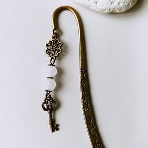 Ásvány könyvjelző kulcs medállal, Otthon & Lakás, Papír írószer, Könyvjelző, Gyöngyfűzés, gyöngyhímzés, 12 cm-es bronz színű könyvjelző matt fehér jáde ásványgyöngyökkel és kulcs medállal.\n\n, Meska