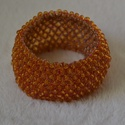 Vastag gyöngy karkötő, Ékszer, óra, Karkötő, Vastag, duplafalú gyöngyből készült karkötő narancssárga színben. 5 cm átmérő., Meska