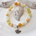 Madárka medálos karkötő ásványokkal és üveggyöngyökkel - sárga, Ékszer, Karkötő, 16 cm-es gumis karkötő sárga és fehér gyöngyökkel, valamint madárka medállal.  A karkötőhöz fehér és..., Meska