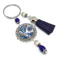 Kék örvény bojtos üveglencsés kulcstartó táskadísz , Mindenmás, Dekoráció, Kulcstartó, Ünnepi dekoráció, Krém és kék gyöngyökből, virágos indás mintával díszített üveglencsés kabosonból és kék velúrbojtból..., Meska