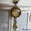 Violinkulcs üveglencsés nyaklánc, Ékszer, Nyaklánc, 20 mm átmérőjű, gyöngyház fényű lencse lapul a sodrott szélű antik bronz színű medálban..., Meska