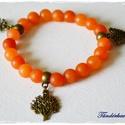 Melengető napsugár matt jáde karkötő, Ékszer, Karkötő, 8 mm matt narancs színű jáde gyöngyök sorakoznak a gumis damilon. A köztes antik bronz színű..., Meska
