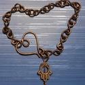Szivecskés karkötő, Ékszer, Karkötő, Antikolt vörösréz drótból s bronz színű díszből készítettem. A kerülete: 19cm., Meska